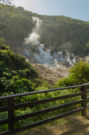 A small fence in the forground frames this live volcano smoking at Soufriere, Saint Lucia. The smoke rolls up the tropical rainforest hill.
