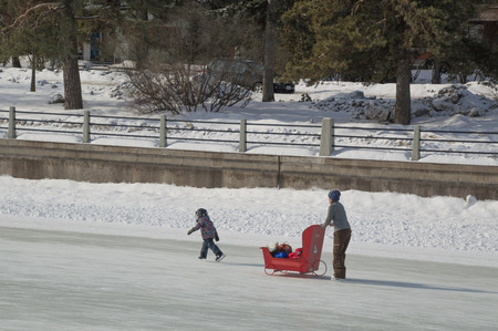 niño empujando: Mom pushing a red sleigh stroller, with young child skating on Rideau canal in the sunshine.