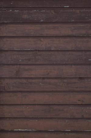 Horizontale lopende grungy bruin gekleurd geschilderde planken en planken van een cottage aan het water.