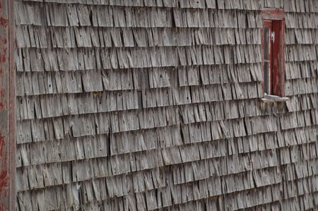 Old weathered cedar shakes shingles barn with red window winter