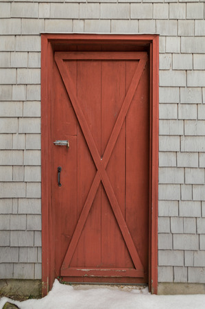 oxblood: Oxblood red barn style X door on cedar shakes shingles background. Snow on the ground.