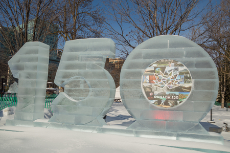 Ice sculpture in Ottawa, on a sunny day with trees behind. Ice carving shows a 150 for Canadas 150th anniversary in 2017