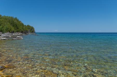 Bright clear aqua green water on Bruce Peninsula. Crystal clear water shows limestone rocks.  Cedar trees and conifers.