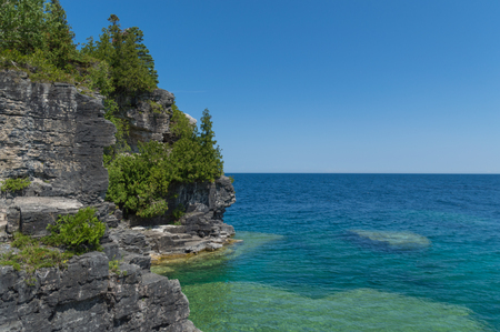Bright clear aqua green water on Bruce Peninsula. Crystal clear water shows limestone rocks.  Cedar trees and conifers.