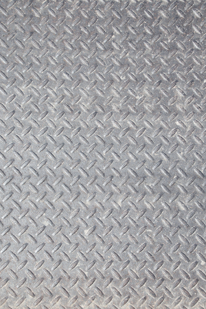 Closeup of a distressed, mottled, gungy industrial diamondplate, chequerplate rusty metal background texture with diamond grip pattern perfect for wallpaper for the construction, heavy equipment and industrial companies.