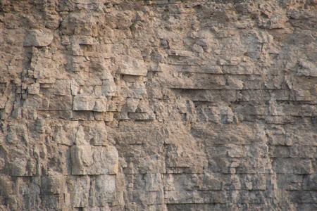 Closeup limestone rock face showing weathered strata and details for geology walpaper or background. Landscape orientation