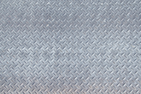 Closeup landscape of a distressed, mottled, gungy industrial diamondplate, chequerplate rusty metal background texture with diamond grip pattern perfect for wallpaper for the construction, heavy equipment and industrial companies. Stock Photo