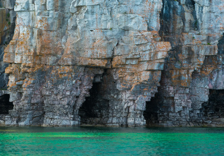 Bright clear aqua green water on Bruce Peninsula with big limestone caves in the cliff at CyprusLake National Park