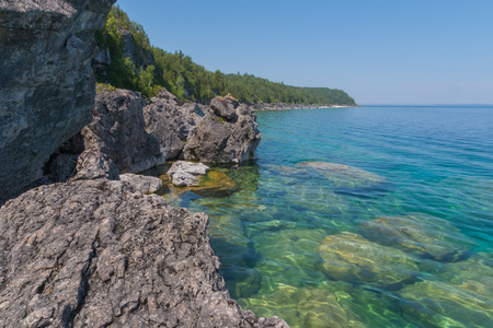 Bright clear aqua green water on Bruce Peninsula. Crystal clear water shows big limestone rocks and cliff