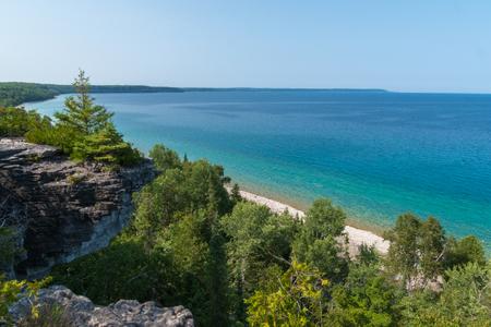 Bright beautiful landscape of Niagara Escarpment limestone cliffs along the blue lake huron shore 스톡 콘텐츠