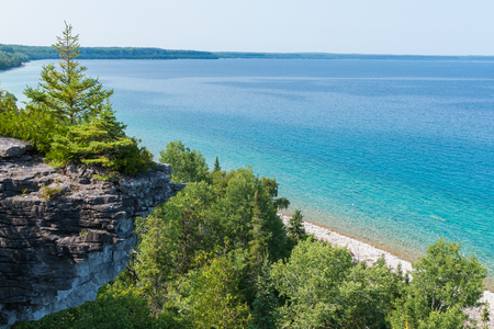 Bright beautiful landscape of Niagara Escarpment limestone cliffs along the blue lake huron shore Imagens