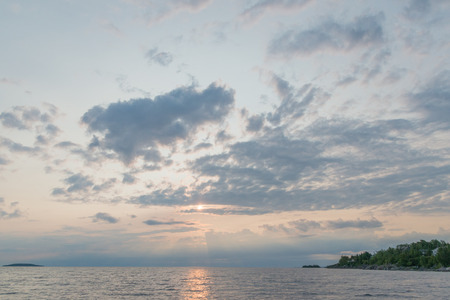 Gorgeous dawn clouds and sunrise on Georgian bay water with cliffs and moody feel Imagens
