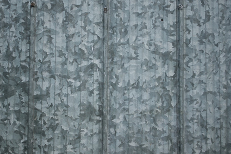 Grungy old galvanized steel panels on a barn with large pattern wallpaper backdrop