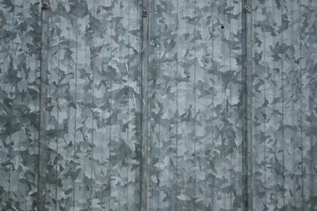 Paneles de acero galvanizado viejo sucio en un granero con telón de fondo de papel tapiz de patrón grande