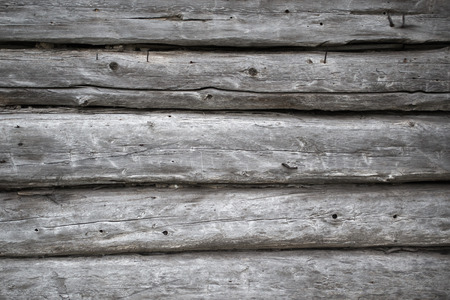 Rough old weathered log cabin background wall closeup with logs and weathered wood grain silvered Stock Photo