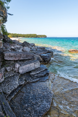 Bruce Peninsula shoreline at Cyprus lake national park on a sunny day with clear blue aqua water Imagens