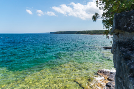 Bruce Peninsula shoreline at Cyprus lake national park on a sunny day with clear blue aqua water 写真素材