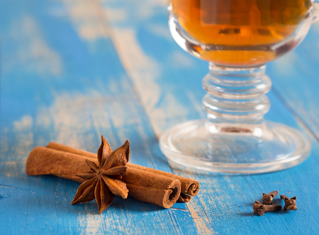 Therapeutic tea with spices in a glass mug on blue wooden boards. Lie cinnamon sticks, carnations. Stock Photo