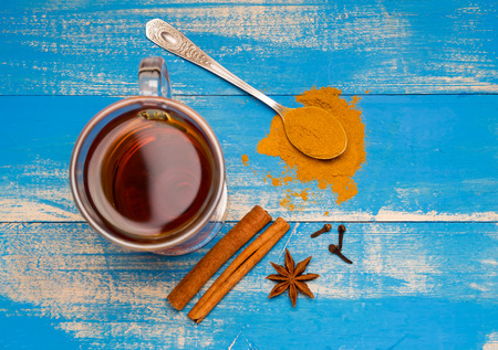 Therapeutic tea with spices in a glass mug on blue wooden boards. Nearby lie cinnamon sticks, carnations and spoon with ground cardamom. Top of view.