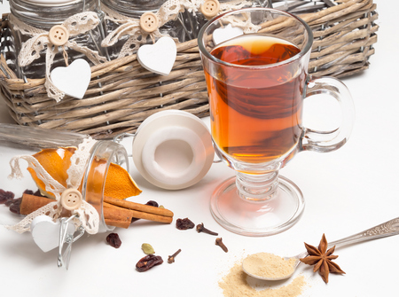 Medical tea with spices in a glass mug on a white background. Next basket with jars and spices: cinnamon, cardamom, orange, cloves. Spoon with ginger.