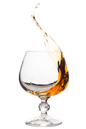 Splash of brandy in glass, isolate. Stock Photo
