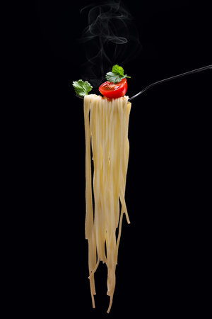 Hot spagetti on the fork with tomato and parsley on the black background.Vertical. Stockfoto