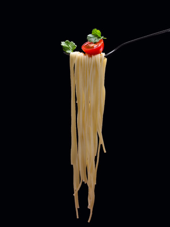 Spagetti on the fork with tomato and parsley on the black background.Vertical.