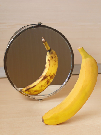 The mirror reflects a spoiled banana. Concept: stress, fatigue, sickness, old age.