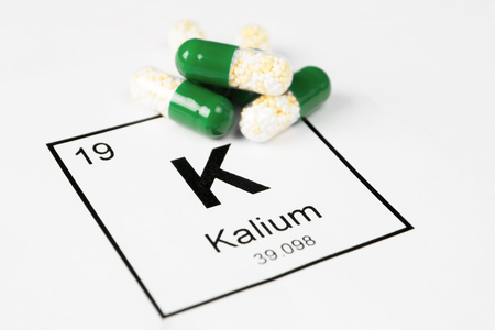 Pills with mineral K (potassium, kalium) on a white background with an inscription from the chemical table