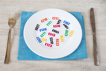 Harmful food additives. There are several tables with the code E-additives on the plate.