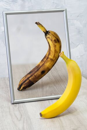 The mirror reflects a spoiled banana. Concept: stress, fatigue, sickness, old age. Archivio Fotografico - 99303099