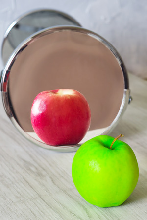 Green apple next to the mirror, the mirror reflects a red apple. Concept: Dont let Yourself to be deceived. Stock Photo