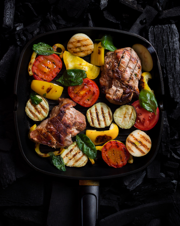 Grilled vegetable and meat on a grill pan on charcoal. Top view.