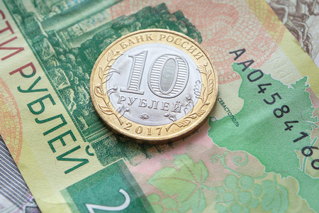 Russian commemorative coin ten rubles on a banknote. Close-up. Фото со стока