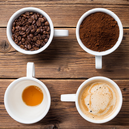 Coffee beans, ground coffee, ready coffee and an empty cup on wooden boards. Square photo, top view.