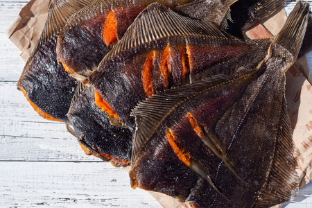 Dried flounder. A stack of dried flatfish with caviar on a light wooden background Standard-Bild - 117117475