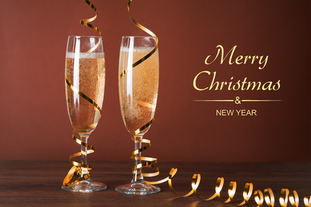 Two glasses of champagne and Christmas decorations on a brown background. Standard-Bild - 117117479