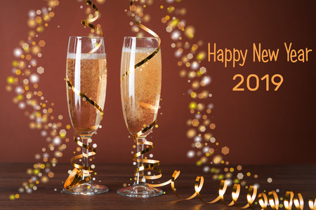Two glasses of champagne and Christmas decorations on a brown background. 2019, Happy New Year. Standard-Bild - 117117480