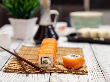 Rolls with salmon on a bamboo mat. Standard-Bild - 117117549