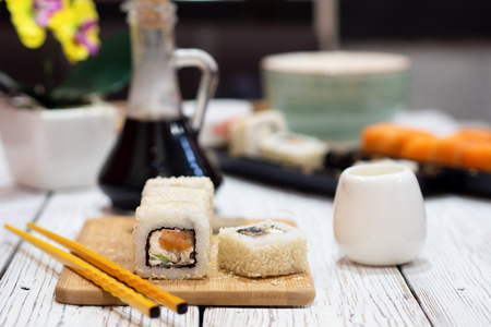 Rolls in sesame on a bamboo board. Near yellow chopsticks. Standard-Bild - 117117590