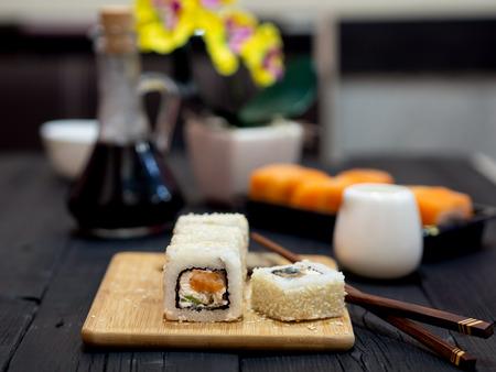 Rolls in sesame on a bamboo board. Near yellow chopsticks. Black wooden table. Standard-Bild - 117117591