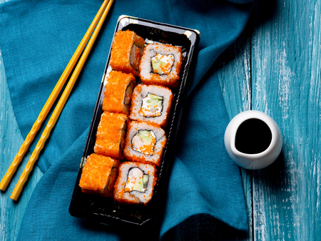 Rolls with shrimp, caviaron and avocado on blue wooden background. Biside chopsticks, towel and sauce Standard-Bild - 117117594