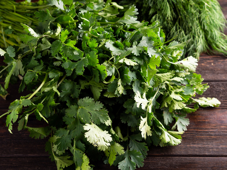 A bunch of fresh parsley on a brown wooden background. Suitable for catalog Standard-Bild - 117117645
