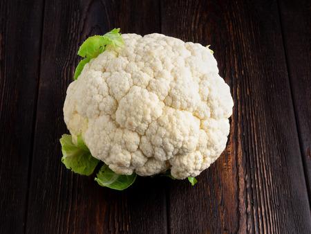Cauliflower on a dark brown wooden background. Standard-Bild - 117117646