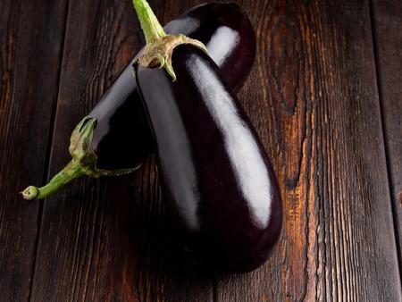 Eggplant on a dark brown wooden background. Standard-Bild - 117117653