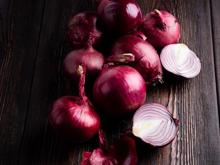 Red onion on a dark brown wooden background. Standard-Bild - 117117659