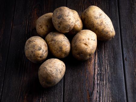 Potatoes on a dark brown wooden background. Standard-Bild - 117117672