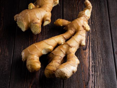 ginger root on a dark brown wooden background. Standard-Bild - 117117674
