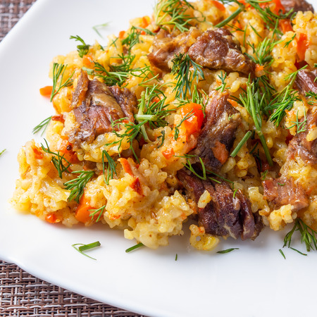 traditional pilaf on a white plate Standard-Bild - 117117675