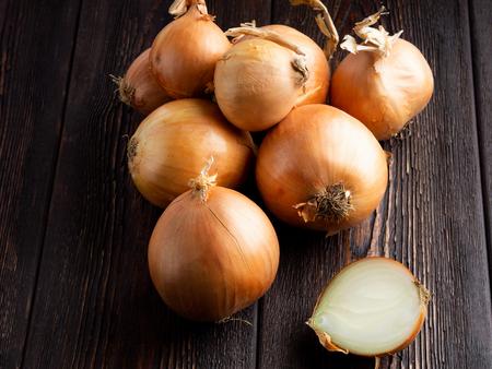 Onion on a dark brown wooden background. Standard-Bild - 117117711